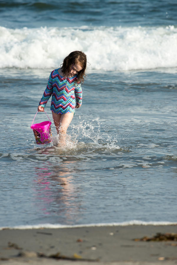 Young cute little girl playing at the seaside carrying a red bucket at the edge of the surf on a sandy beach in summer royalty free stock photos