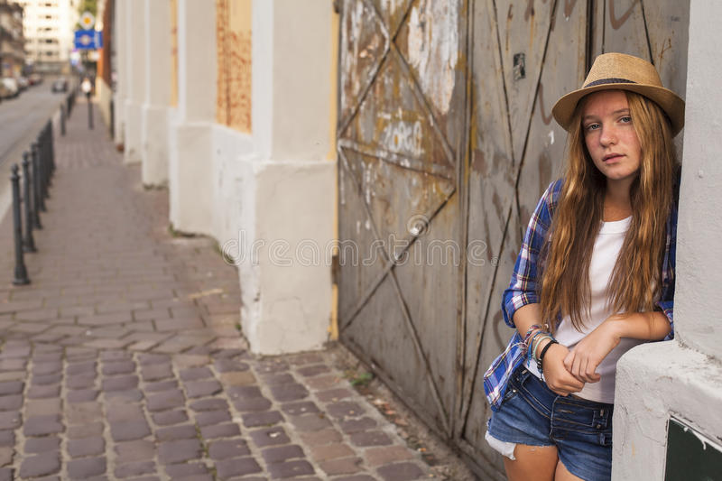 Young cute long haired girl standing on a street corner in shorts and hat. Walk. royalty free stock photography