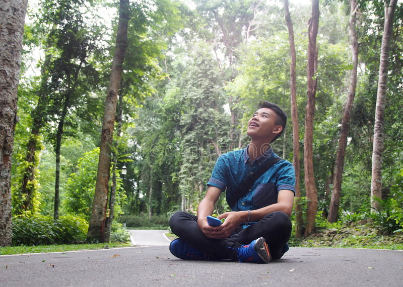 Young cute male healthy teenager asian boy wearing shiny blue shirt royalty free stock photo