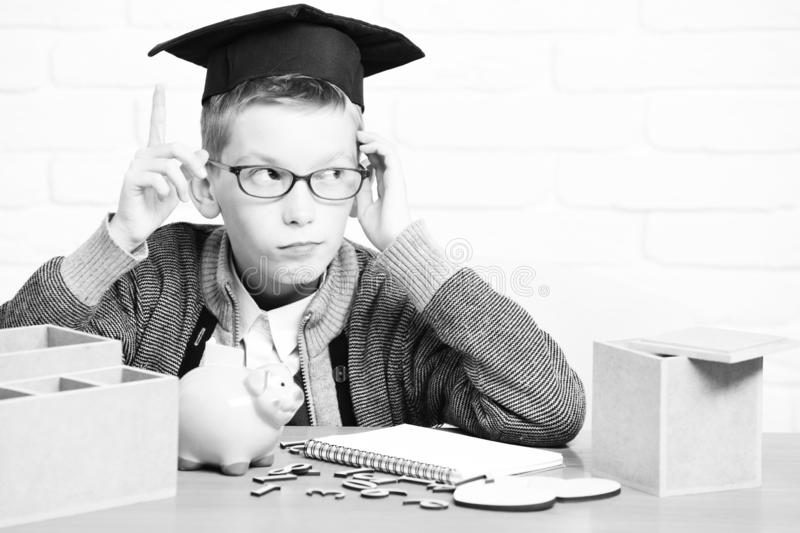 Young cute pupil boy in grey sweater and glasses sitting at desk with copybook wooden numbers pink piggy pig bank in royalty free stock images