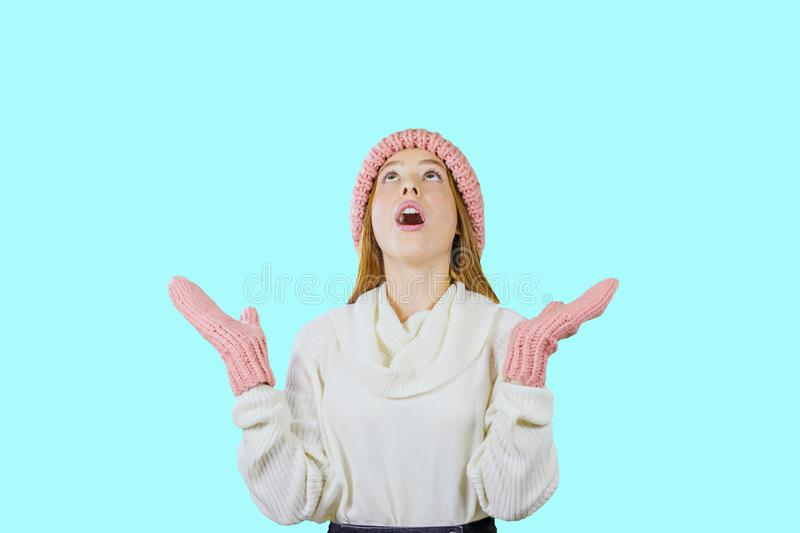 Young cute red-haired teenager girl in a knitted pink hat and mittens holding her hands up looks up with surprise with royalty free stock photos