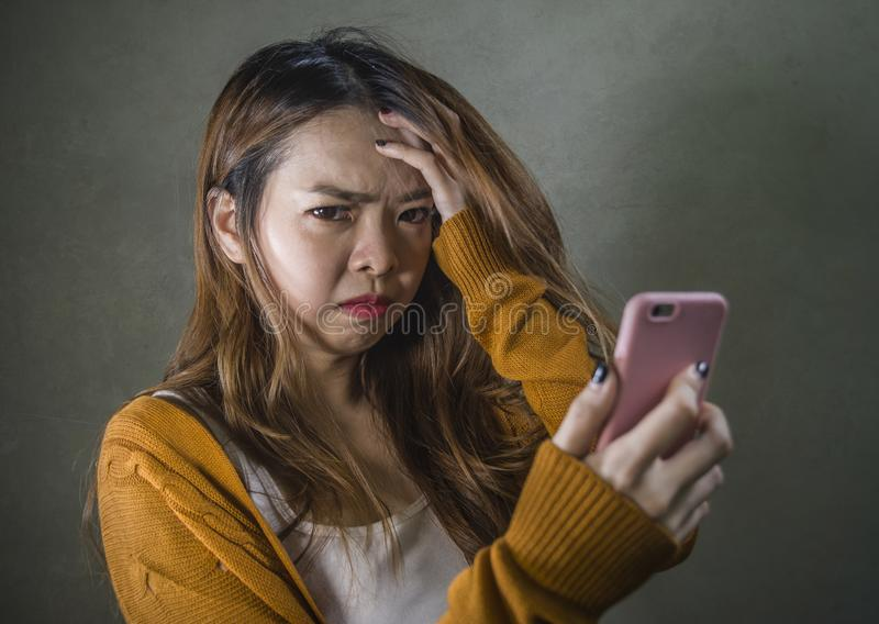 Young cute and sad Asian Korean girl feeling broken heart and desperate holding mobile phone suffering relationship break up. Dumped via internet message royalty free stock image