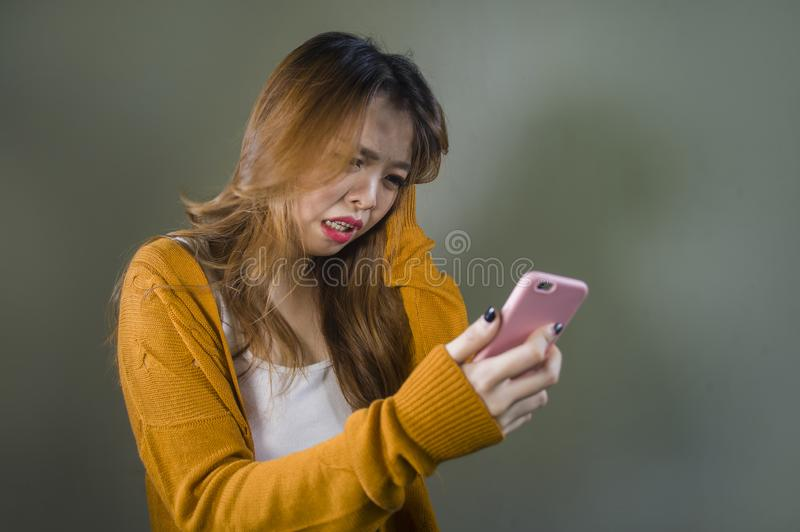 Young cute and sad Asian Korean girl feeling broken heart and desperate holding mobile phone suffering relationship break up. Dumped via internet message stock image