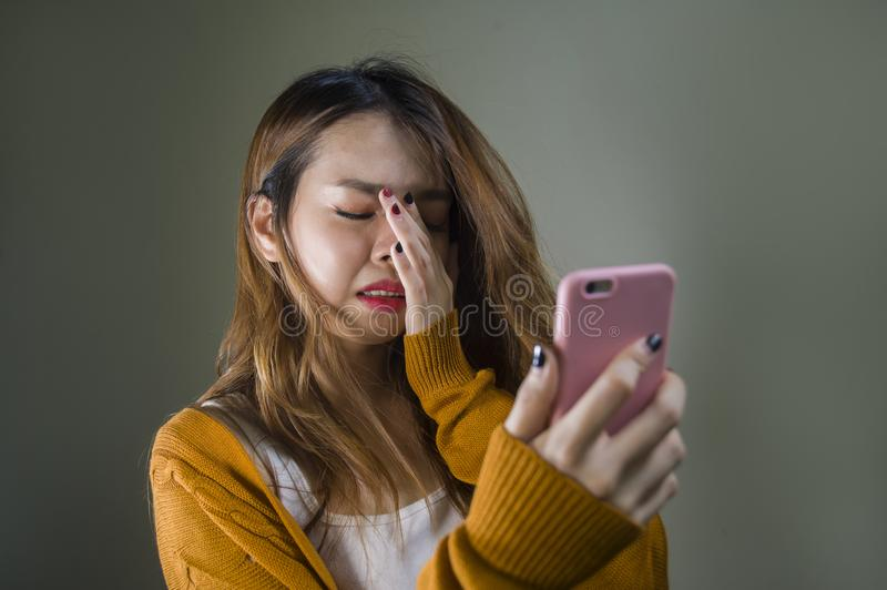 Young cute and sad Asian Korean girl feeling broken heart and desperate holding mobile phone suffering relationship break up. Dumped via internet message royalty free stock photo