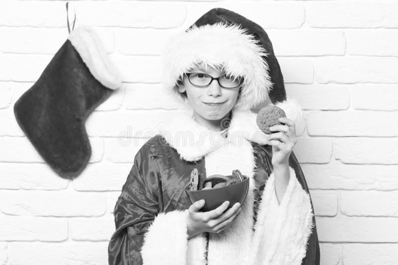 Young cute santa claus boy with glasses in red sweater and new year hat with decorative christmas or xmas stocking or. Boot holding chocolate hip cookies in stock photos