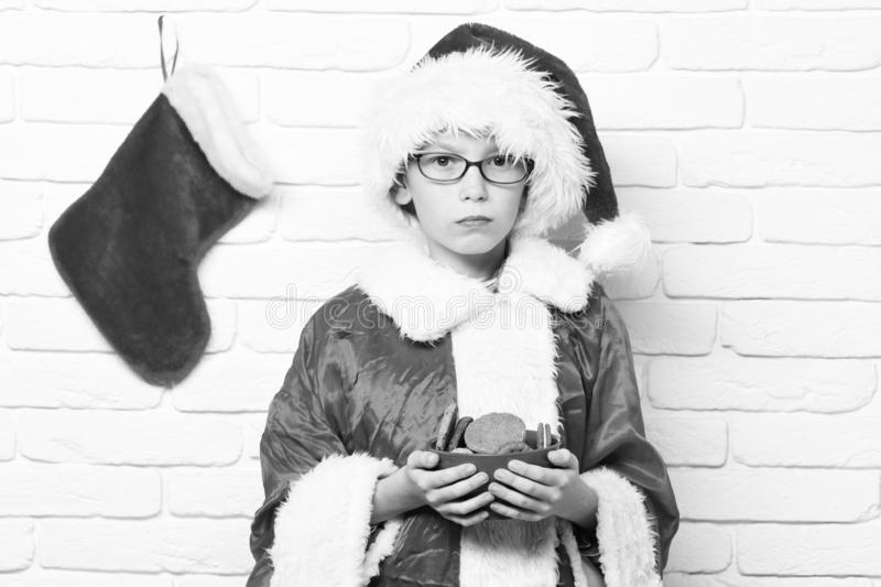 Young cute santa claus boy with glasses in red sweater and new year hat with decorative christmas or xmas stocking or. Boot holding chocolate hip cookies in royalty free stock photo