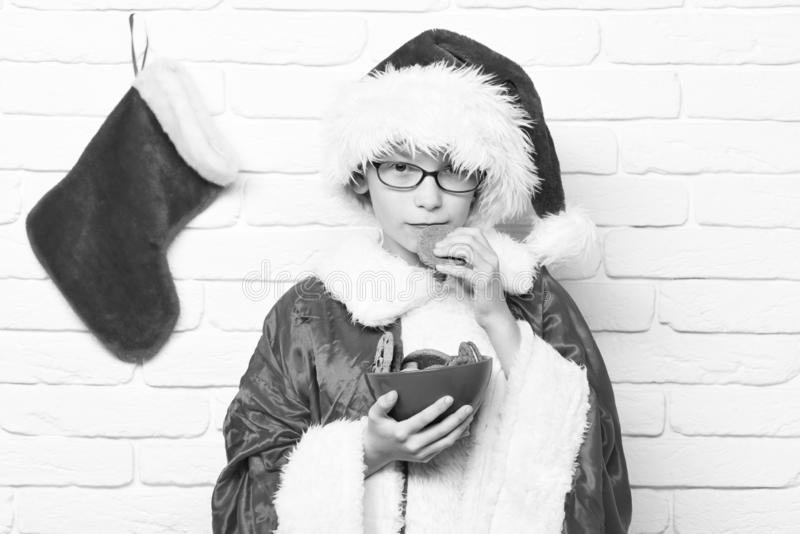 Young cute santa claus boy with glasses in red sweater and new year hat with decorative christmas or xmas stocking or. Boot holding chocolate hip cookies in stock photography