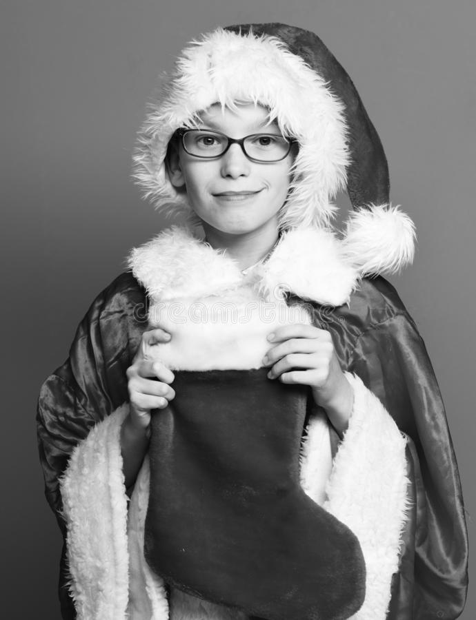 Young cute santa claus boy with glasses in red sweater and new year hat holds decorative christmas or xmas stocking or. Boot on studio background royalty free stock image