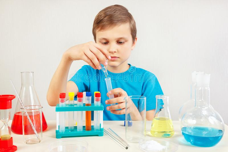 Young cute scientist doing chemical experiments in laboratory. Young cute scientist doing chemical experiments in the laboratory royalty free stock image