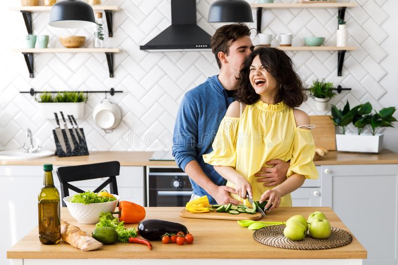 Young cute smiling couple cooking together at kitchen at home. A young woman slicing fresh vegetables on a wooden salad board. royalty free stock images