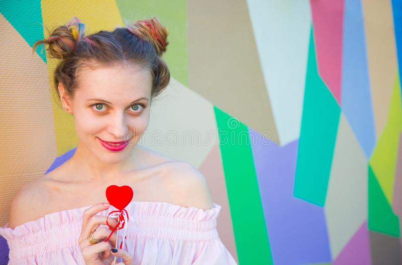 Young cute smiling woman with colorful hair holding red heart in. Her hands on multicolored background. Romantic banner for Valentine's day stock photo