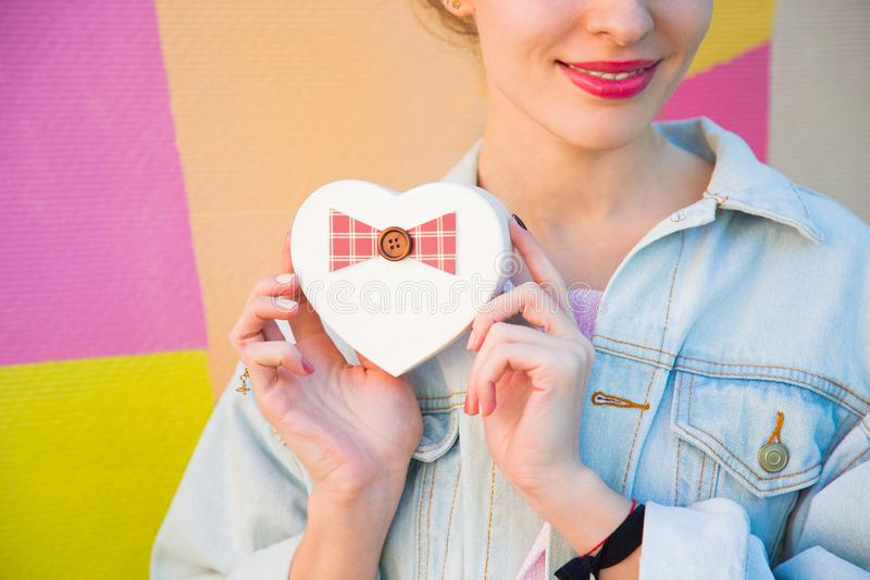 Young cute smiling woman holding gift box in shape of heart in h. Er hands on multicolored background. Romantic banner for Valentine's day royalty free stock photography