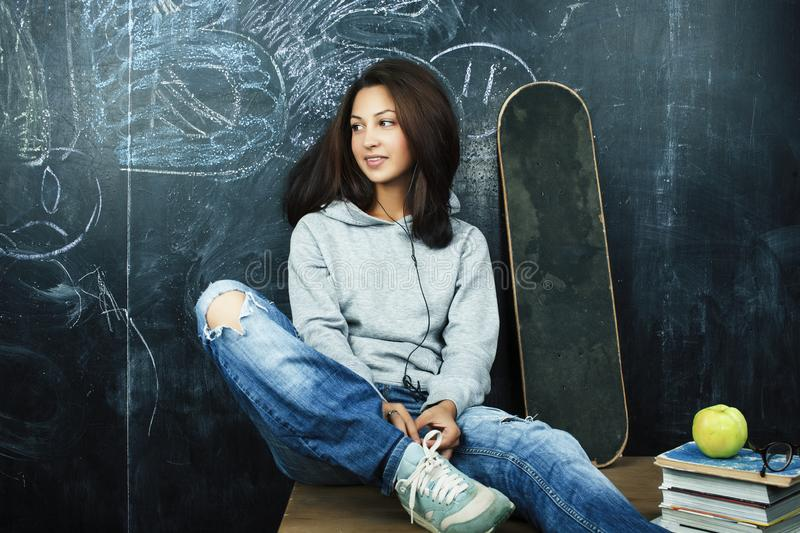 Young cute teenage girl in classroom at blackboard seating on table smiling, modern hipster concept royalty free stock photo