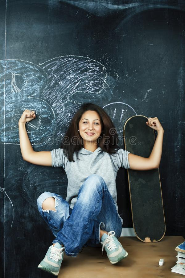 Young cute teenage girl in classroom at blackboard seating on table smiling, modern hipster concept royalty free stock image