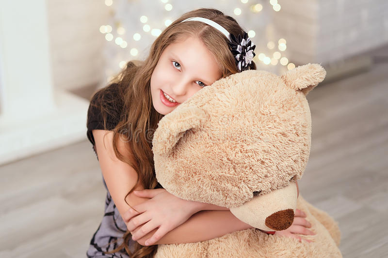 Young cute teenage girl hugs a big soft teddy bear in the interi. Or with Christmas decorations royalty free stock image