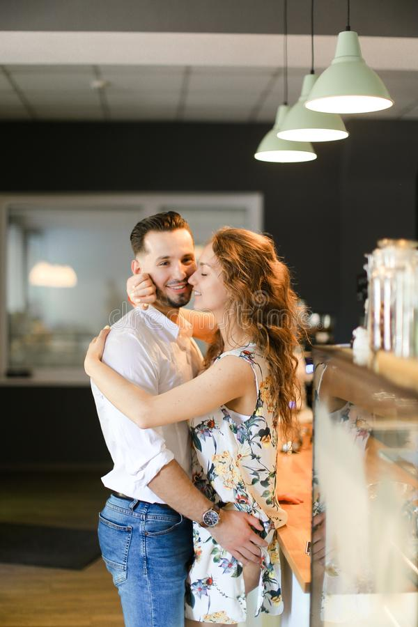 Young cute wife hugging husband at cafe. Young cute wife hugging husband at cafe near bar. Concept of happy couple and contemporary interior stock photography