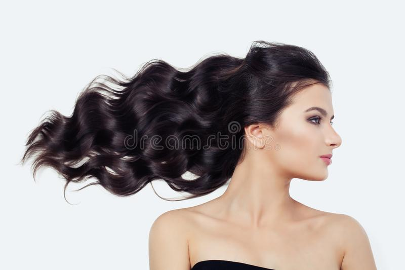 Young cute woman with blowing curly hair on white, brunette beauty girl stock photo