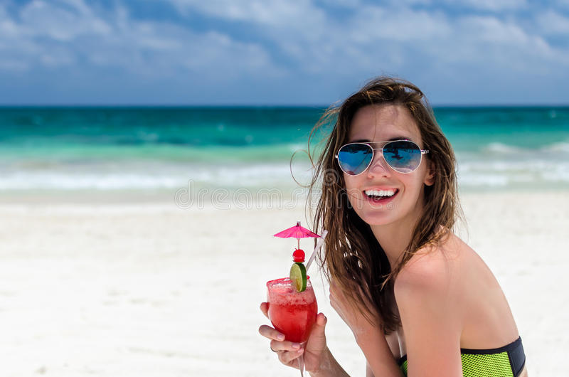 Young cute woman with fresh cocktail at tropical sandy beach stock image
