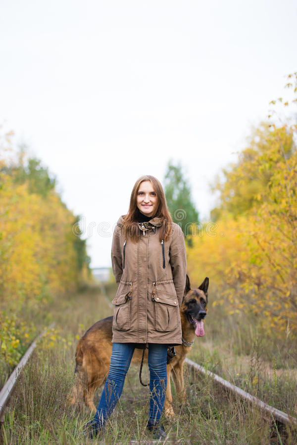 Young cute woman with german shepherd dog posing in autumn forest near rail way. Telephoto royalty free stock photos
