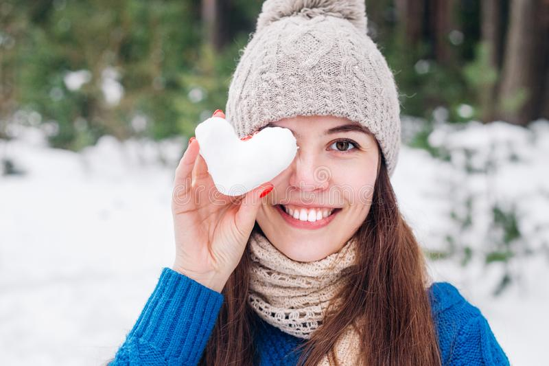 Young cute woman holding snow heart in winter forest. Love concept. Valentine day background. stock photography