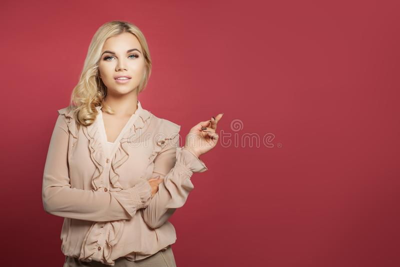 Young cute woman pointing up against pink wall background. Casual student girl pointing finger royalty free stock photos