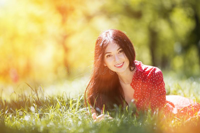 Young cute woman in red dress relaxing in the autumn park. Beauty nature scene with colorful background, trees at fallseason. stock images