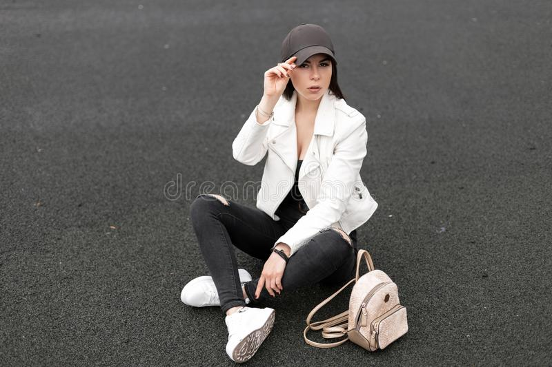 Young cute woman in vintage ripped jeans in a leather jacket in a t-shirt with a gold backpack in fashionable sneakers. In a trendy baseball cap sits on the royalty free stock photography