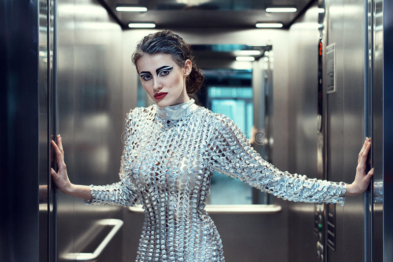 Young cyber woman in silver futuristic costume standing in the elevator. royalty free stock photo