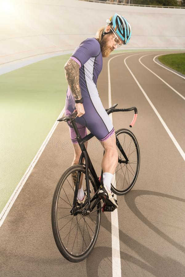 Cyclist on cycle race track. Young cyclist in helmet and goggles looking at bicycle on cycle race track stock photography