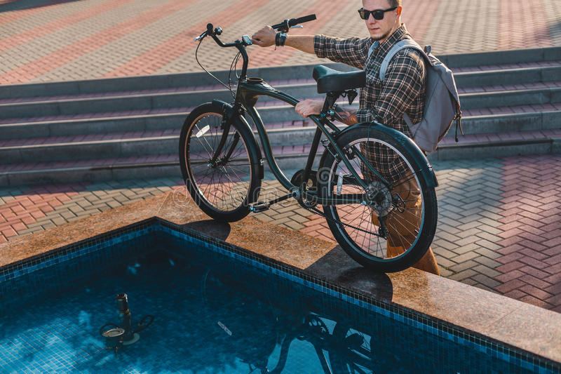 Young Cyclist Put His Bicycle On Edge Of City Fountain Daily Lifestyle Urban Resting Concept. Young Cyclist In Sunglasses With Backpack Put His Bicycle On Edge stock images