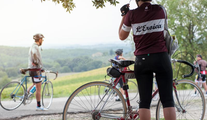 A young cyclist woman takes a break on the roadside, during a cycling race in the Tuscan countryside royalty free stock image