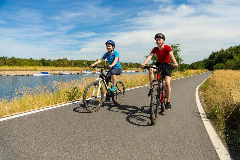Young cyclists. Girl and boy biking on cycle lane royalty free stock images