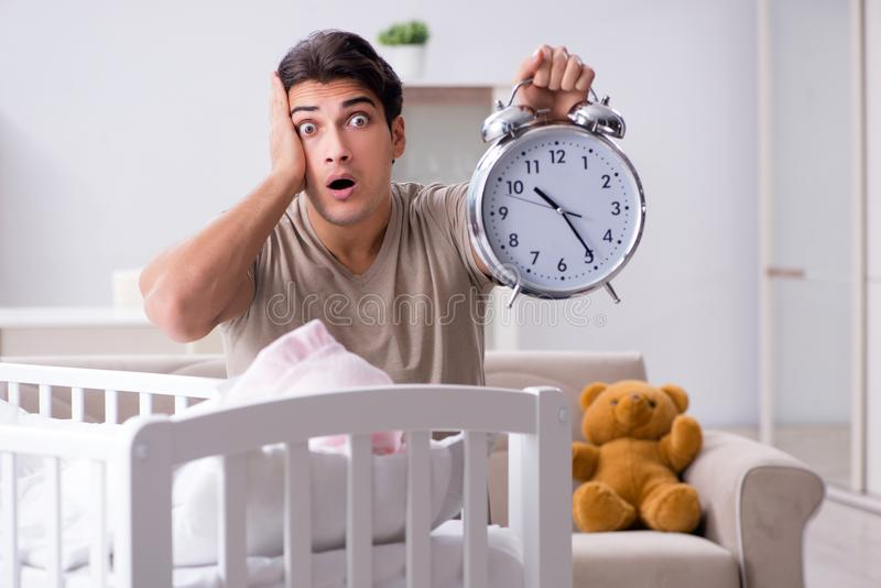 The young dad with clock near newborn baby bed cot. Young dad with clock near newborn baby bed cot stock images