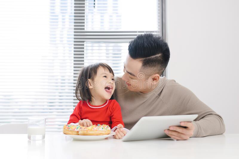 Young dad and his daughter eating pizza and using ipad.  stock images