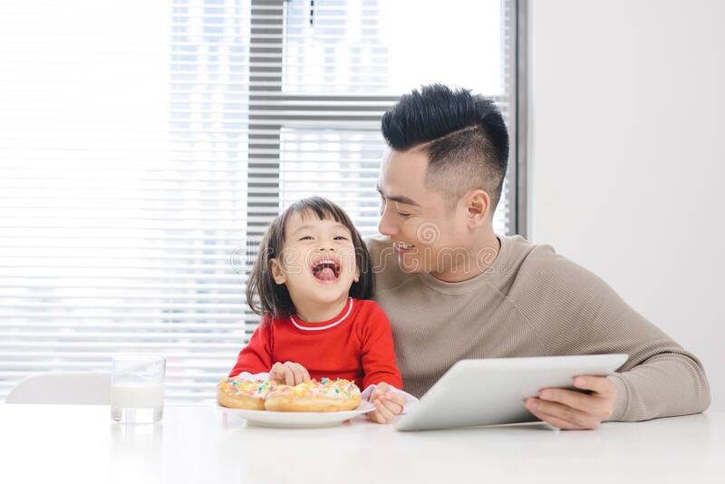 Young dad and his daughter eating pizza and using ipad.  stock photos
