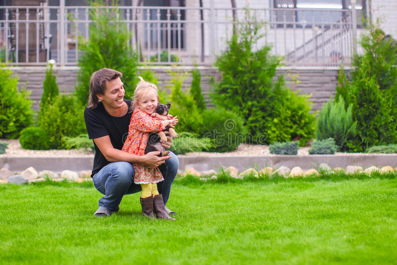 Young dad and his little daughter with her puppy on background their home. Young dad and his little daughter with puppy on background their home royalty free stock image