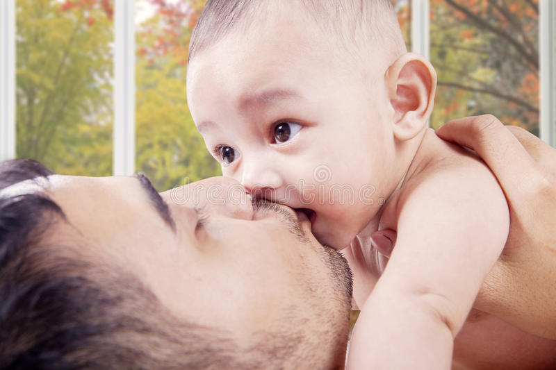 Young dad kiss baby's mouth royalty free stock photos