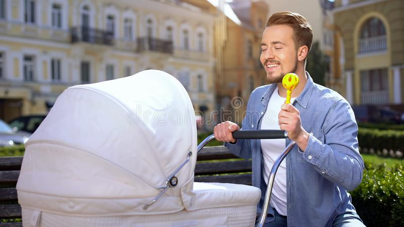 Young dad with rattle toy swinging baby stroller, good father, child care, love. Stock photo stock photos