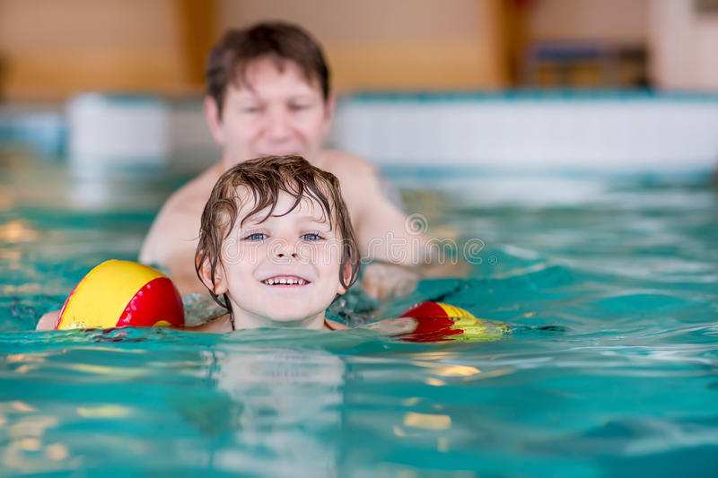 Young dad teaching his little son to swim indoors. Young dad teaching his little son to swim in an indoor swimming pool. Active happy kid boy wearing safe royalty free stock image