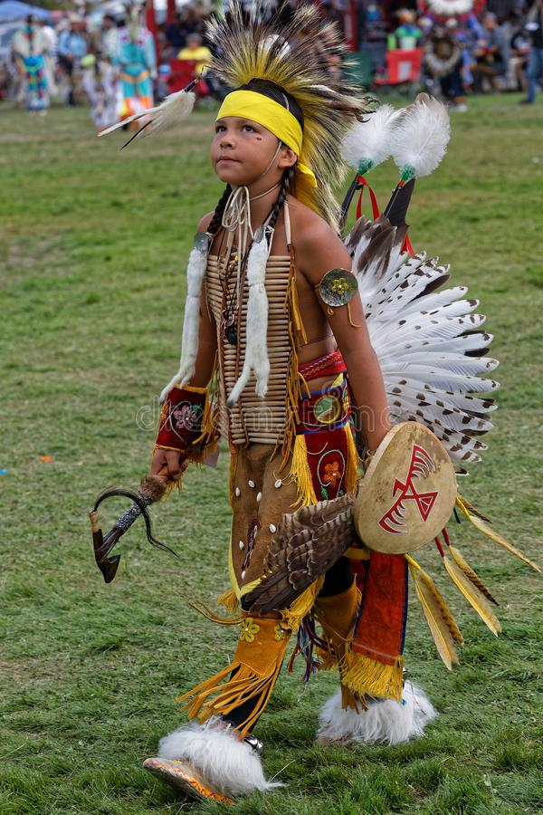 A young dancer back from dance during the 49th United Tribes Pow Wow. BISMARK, NORTH DAKOTA, September 9, 2018 : A dancer of the 49th annual United Tribes Pow royalty free stock photo