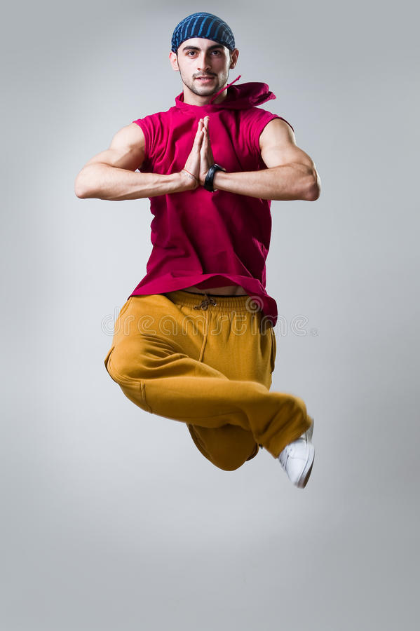 Young dancer jumping over gray background stock image