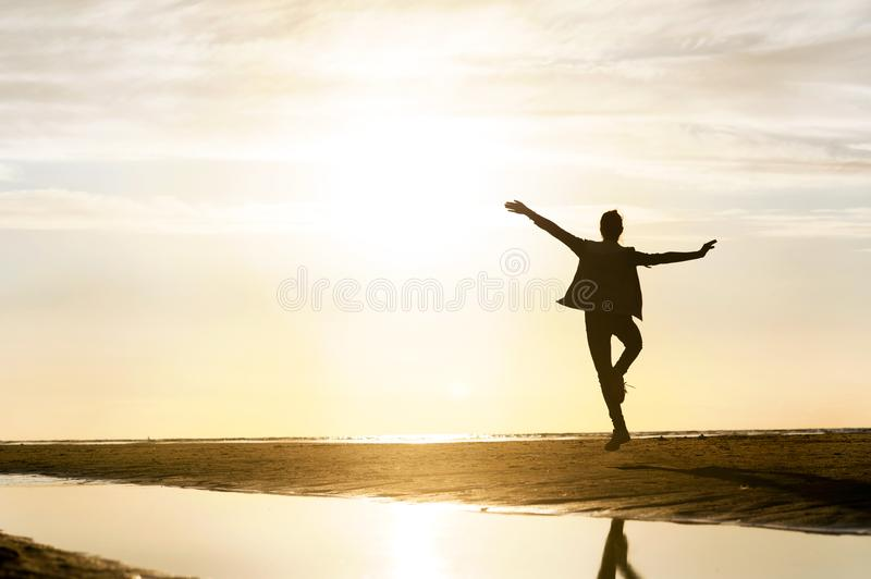 Young dancing girl silhouette in sunbeam at sunset on the beach. royalty free stock photo