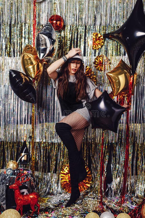 Young dancing woman. Young active dancing woman on a shimmer background. Party hard. Girl holding balloons, ready to celebrate in a space with golden and silver stock images