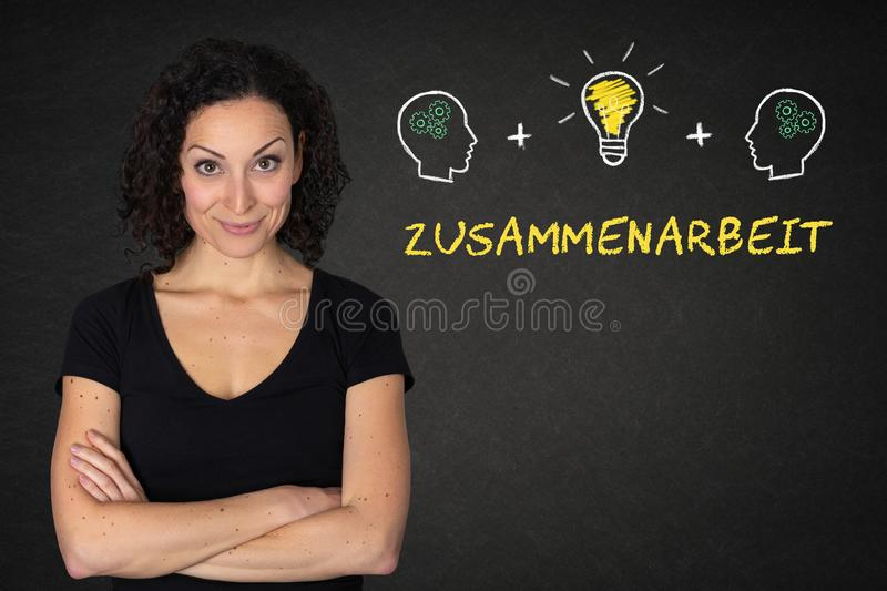 Young woman with crossed arms, heads, bulb-idea & text `Zusammenarbeit`on a blackboard. Translation: & x27;Teamwork& x27;. Young dark curly haired business woman stock photo