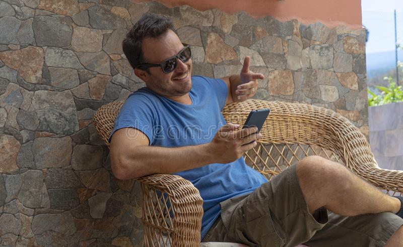 Young dark hair guy making a video call with his cellphone. Blogger taking a selfie with his device. Happy man enjoying sitting in stock photos