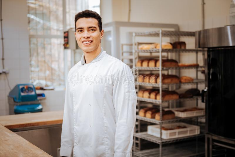 Young dark-haired baker smiling while feeling excited before work royalty free stock images