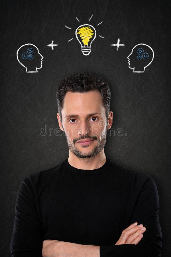 Young man with crossed arms, heads with brains and light bulb idea on a blackboard background. Young dark haired and bearded business man with a black sweater royalty free stock photos