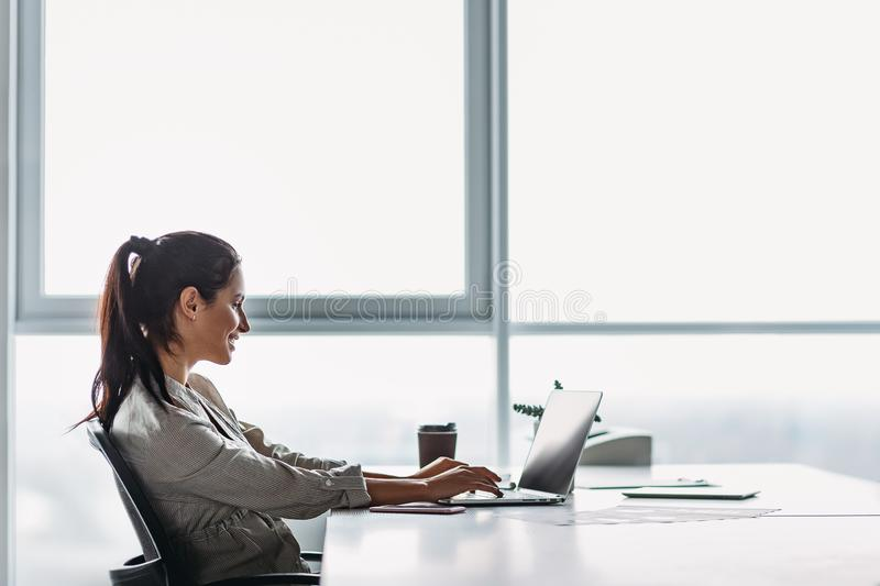Portrait of gorgeous, smiling young female using laptop computer at workplace. Side view. Young dark-haired businesswoman wearing striped shirt is sitting in her royalty free stock photo