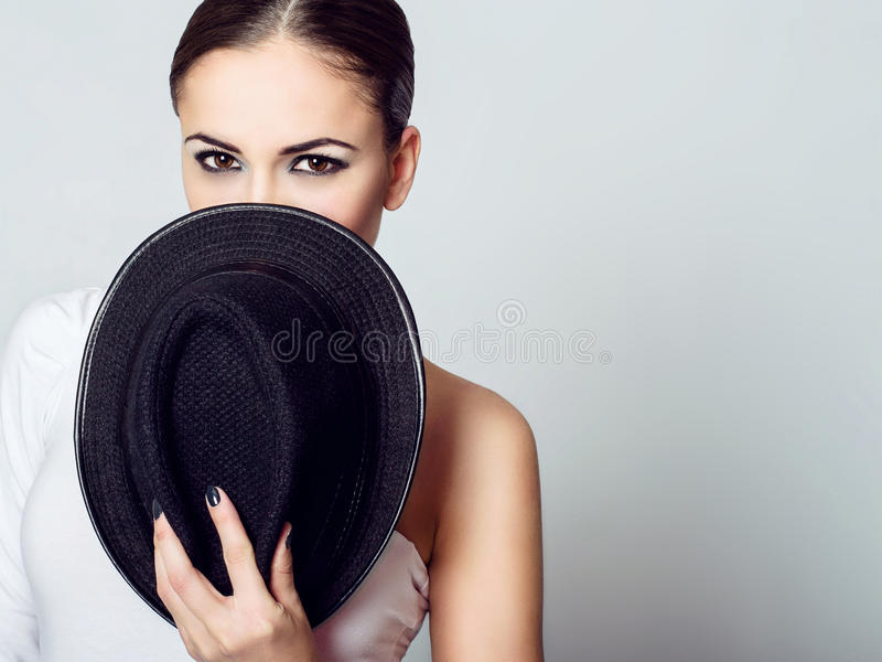 Young dark-haired girl hiding her face behind the hat. stock image