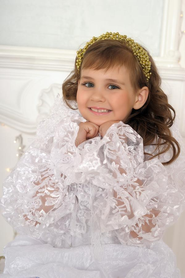 Young dark-haired girl in a smart white princess dress royalty free stock images